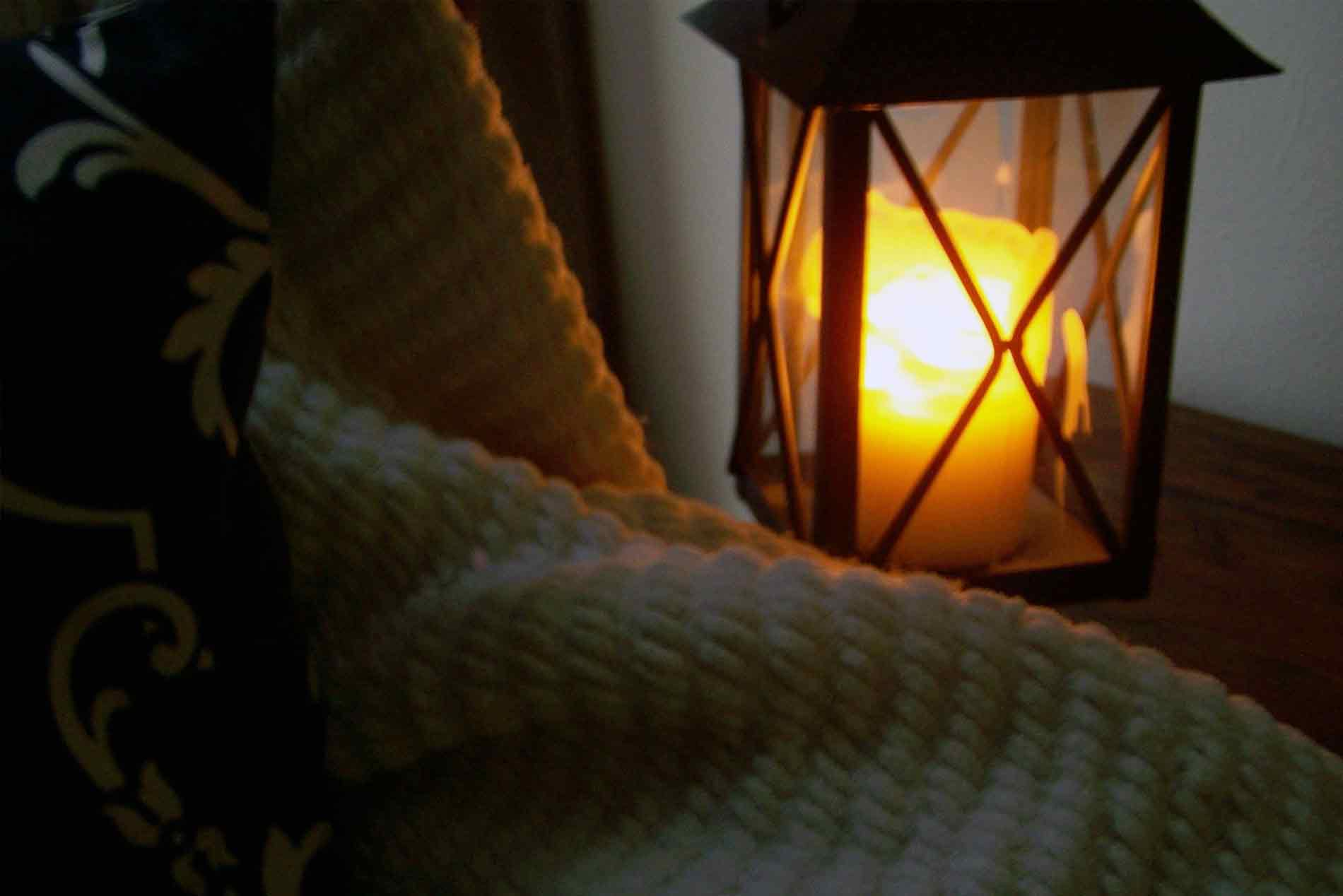 candle lantern next to a blanket