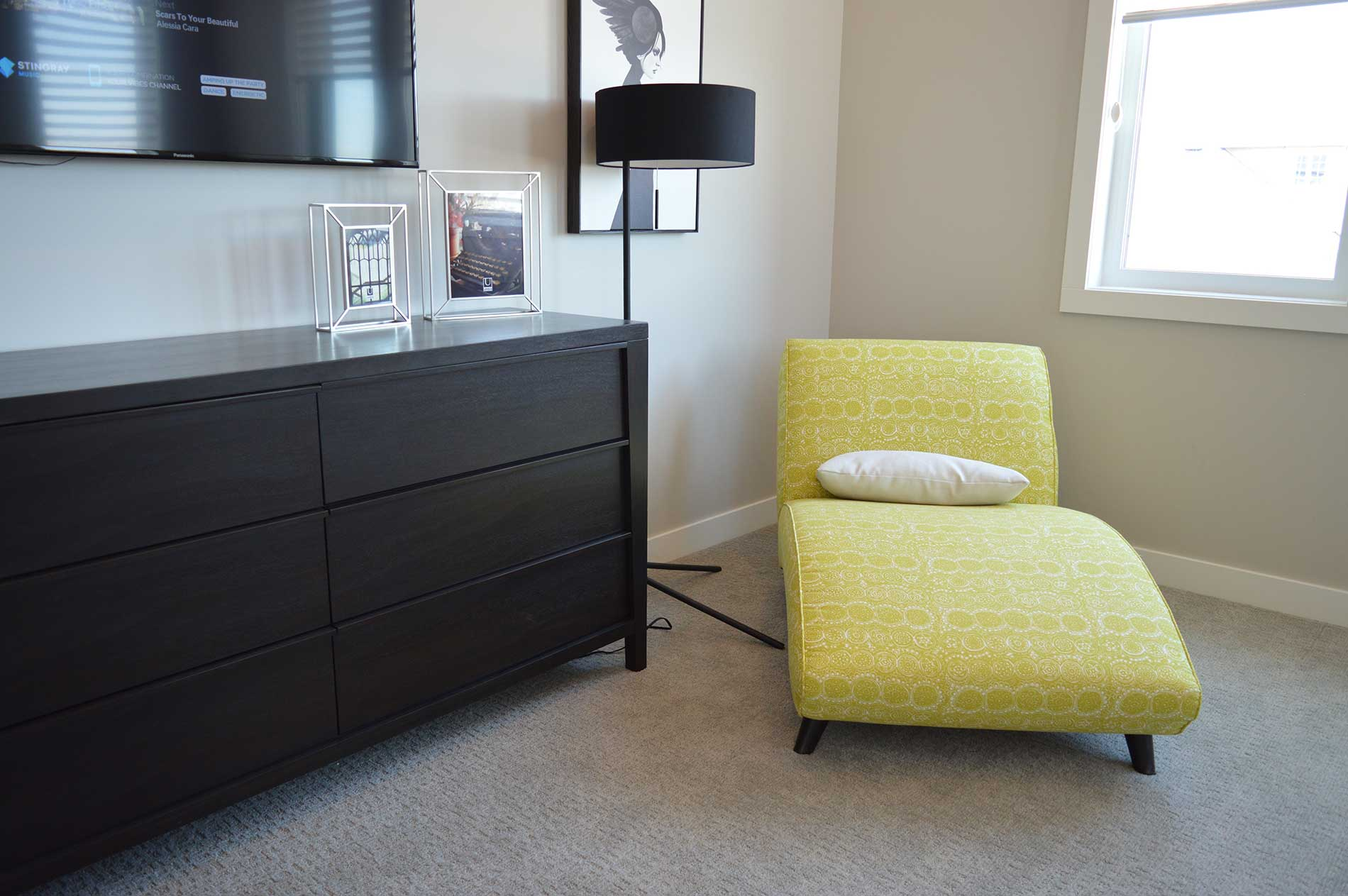Yellow chaise lounge next to a brown dresser